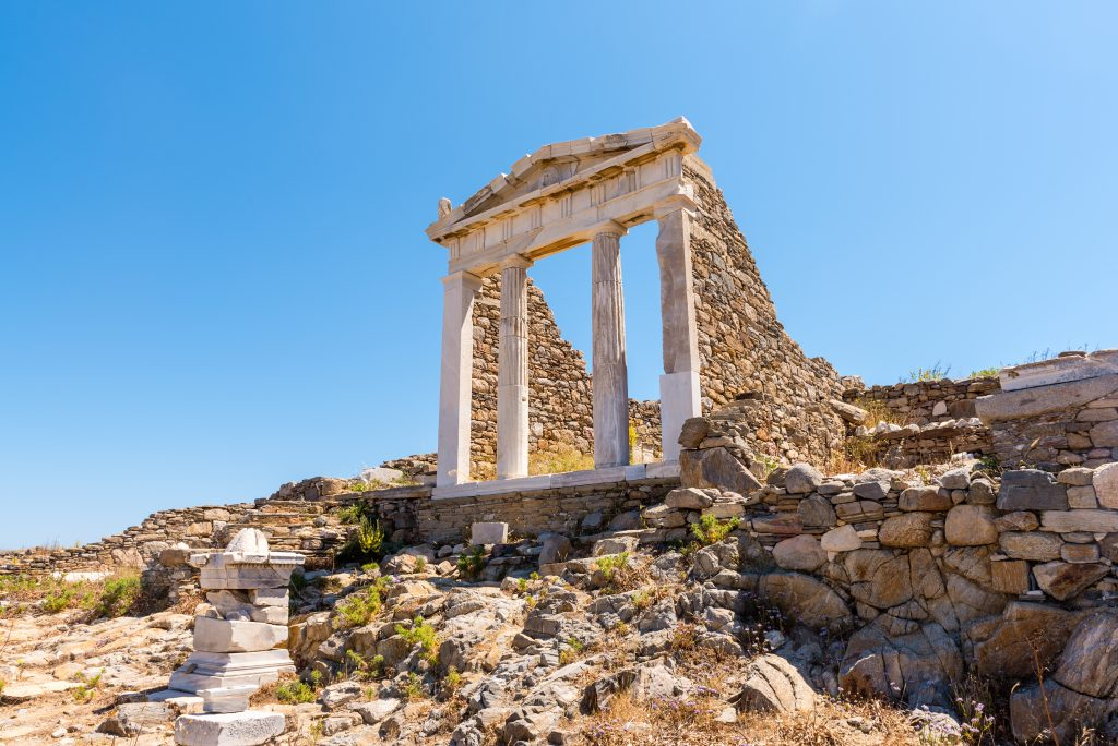 ancient ruins on delos island, with a set of four columns prominent in the photo