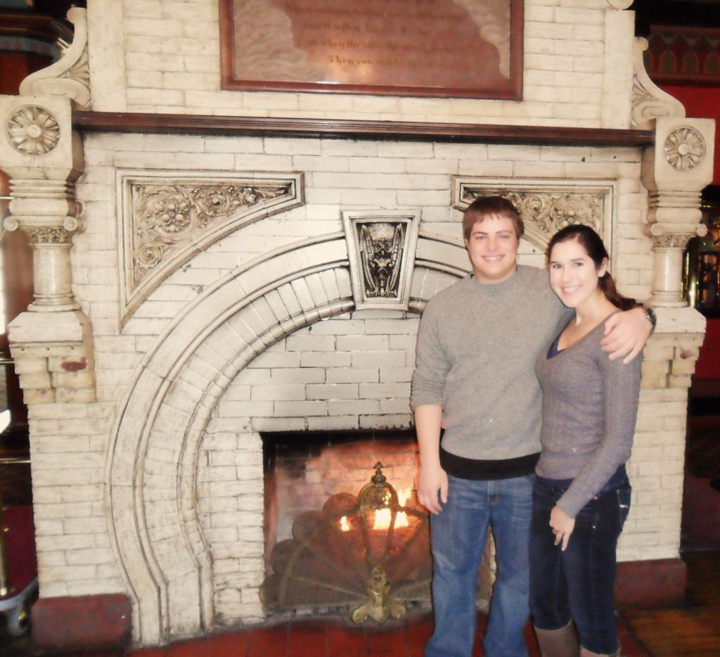 kate storm and jeremy storm in front of a fireplace in crescent hotel eureka springs arkansas