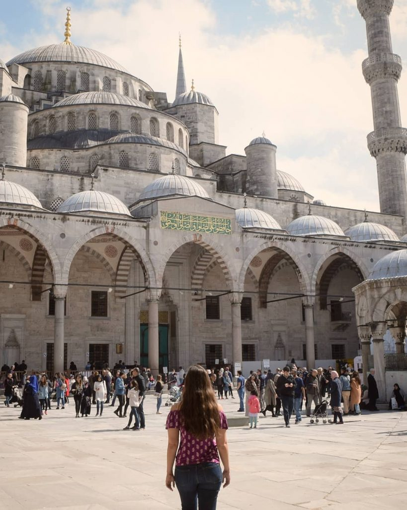 kate storm standing in front of the blue mosque, one of the best things to do in istanbul turkey