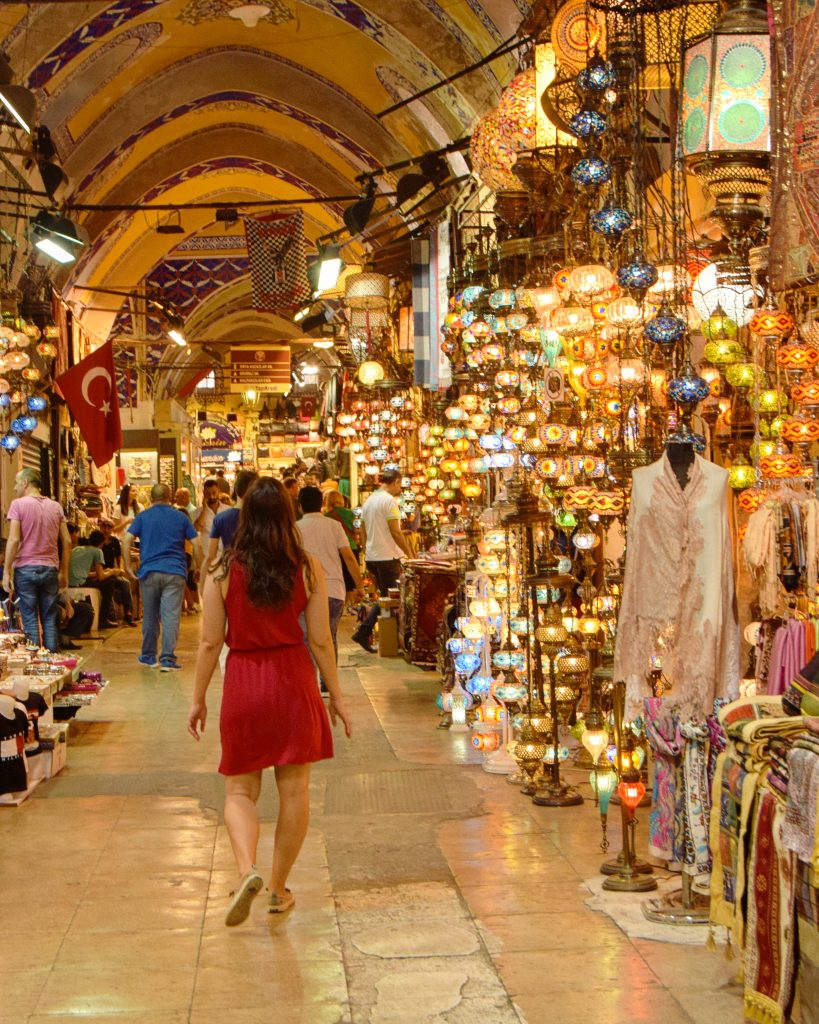 kate storm in a red dress walking through istanbul grand bazaar, one of the best places to visit in istanbul turkey