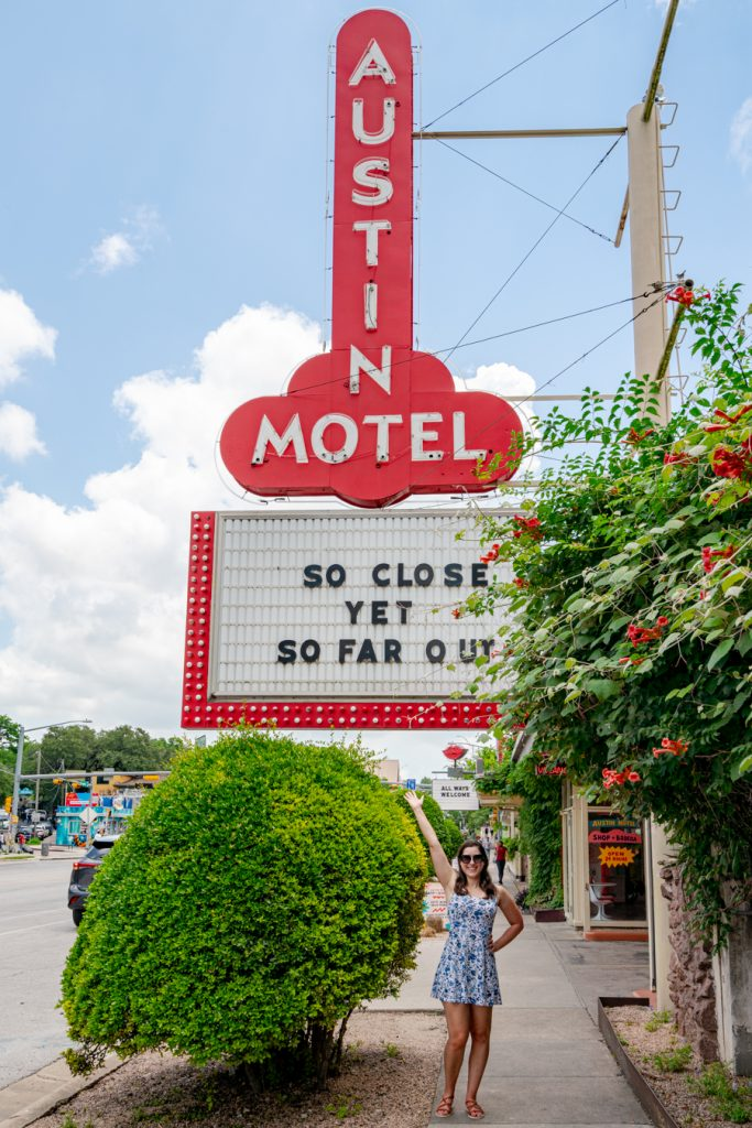 kate storm in a blue and white dress standing under the iconic austin motel sign in austin texas