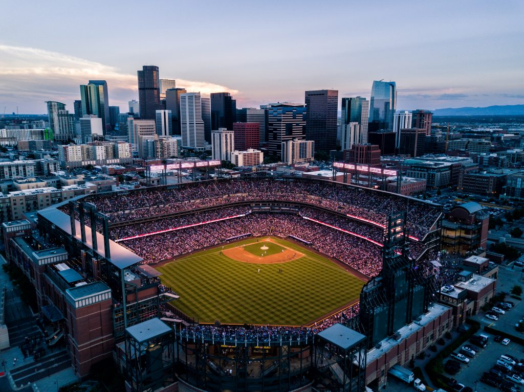 aerial view of a denver rockies game at night with the skyline in the background