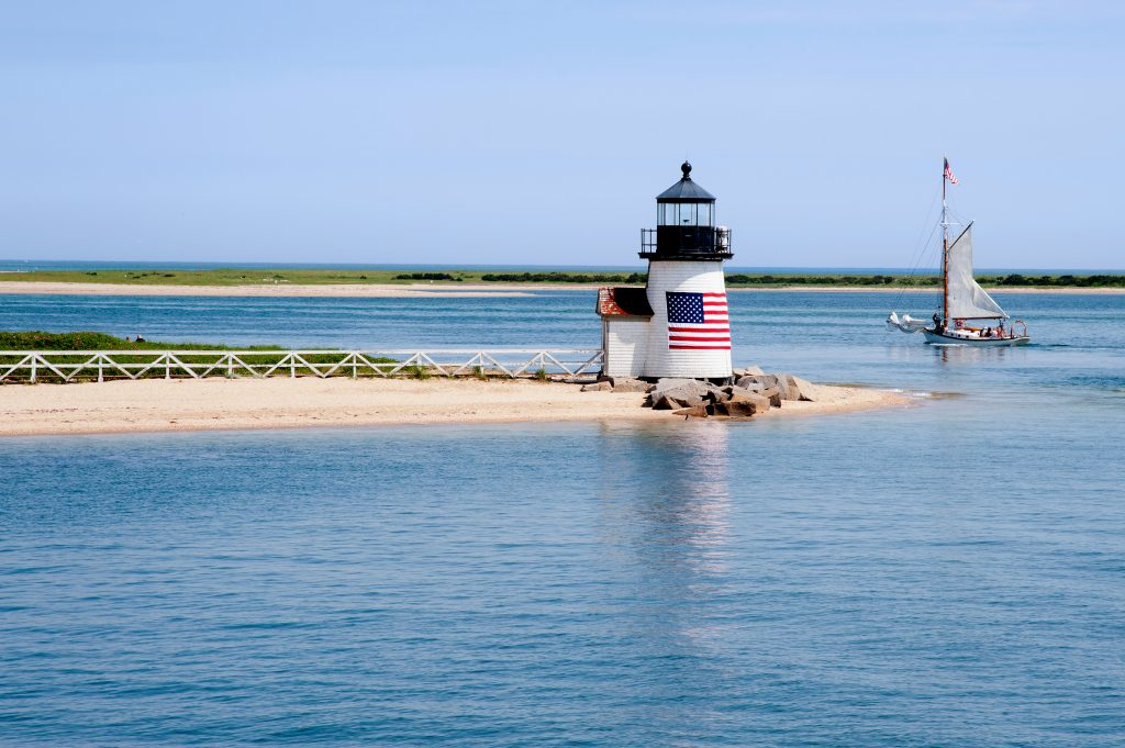 white lighthouse with an american flag on it and a sailboat nearby in nantucket massachusetts, one of the best tourist attractions in usa