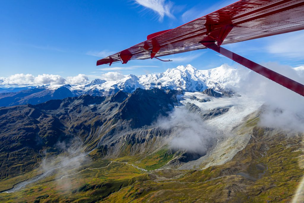 view of snowcapped mountains in alaska from a small red plane on a flightseeing tour, one of the top things to do in usa
