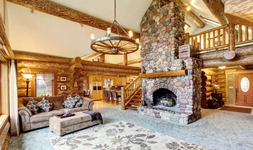 interior of a luxurious log cabin with a stone fireplace in the center