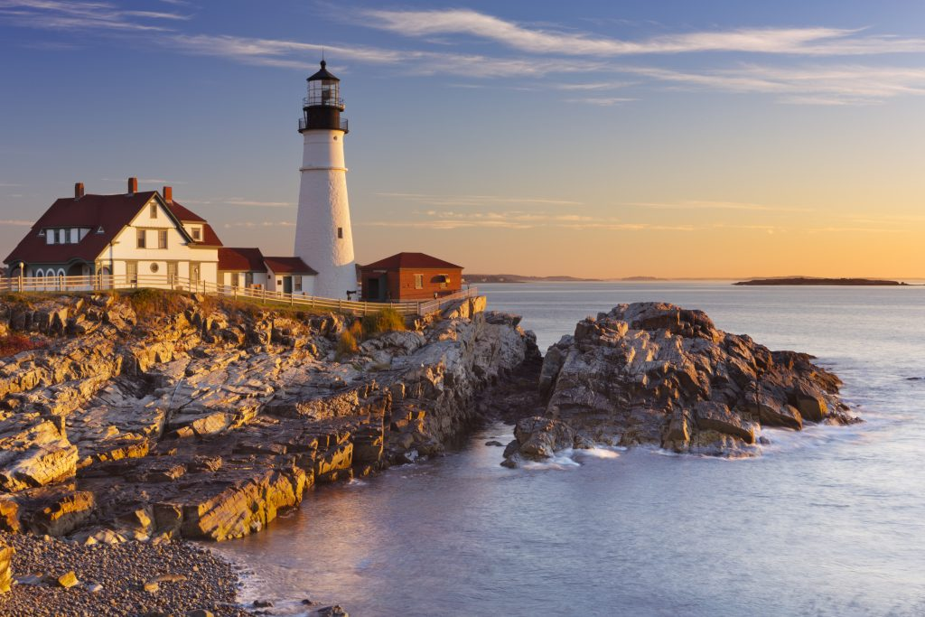 lighthouse in portland maine at sunset with ocean in the foreground, one of the best things to do in the us