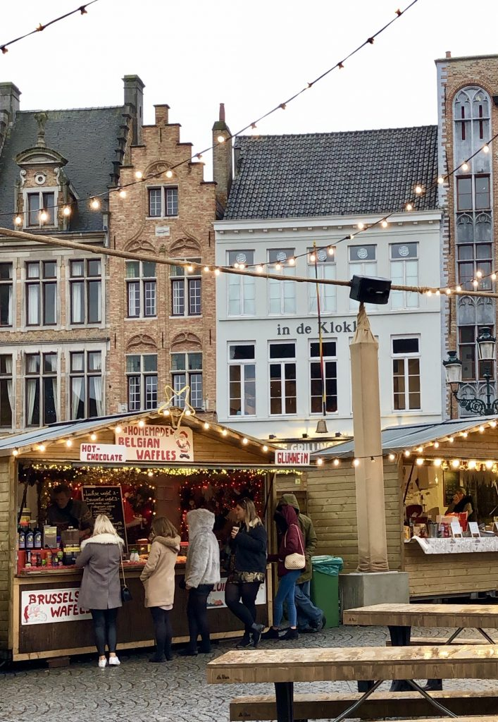 people shopping at a belgium christmas market in bruges