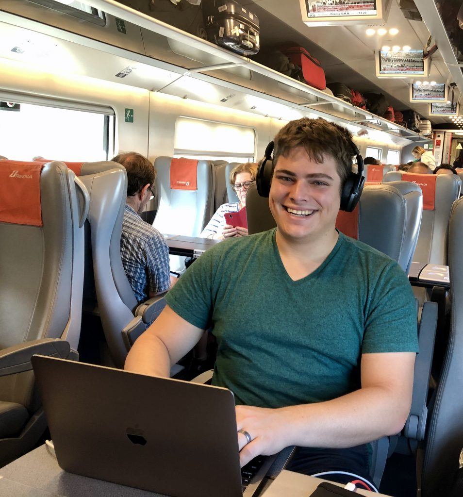 jeremy storm working on a macbook on a train in italy, combining work and traveling