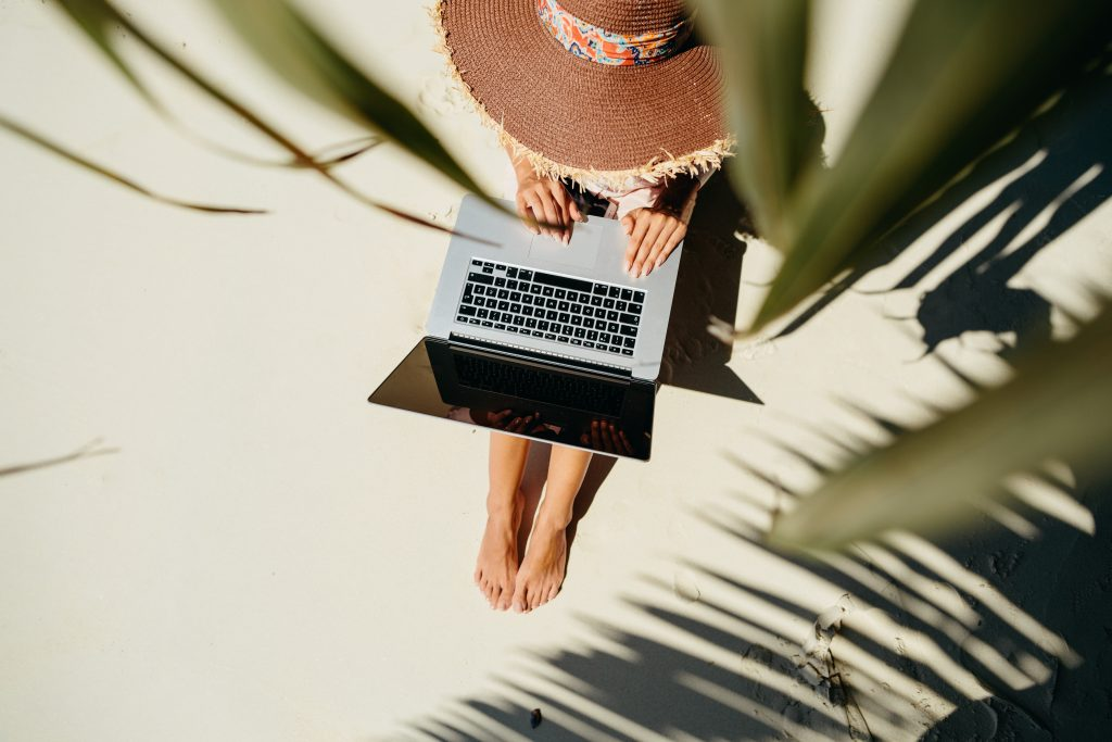 woman working while traveling on the beach